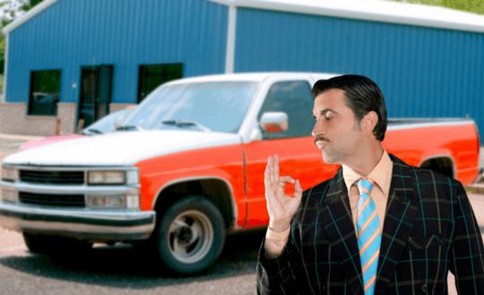 Een gladde 2ehands autoverkoper prijst een oude auto aan.